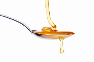 Honig tropft von Löffel