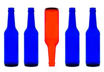 Blaue Flaschen und eine rote Flasche steht Kopf