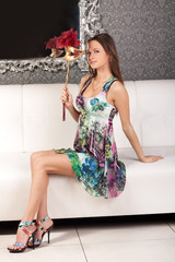 Cute young brunette in a dress holding a mask