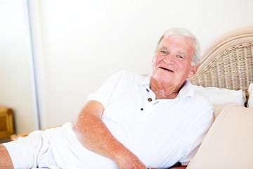 happy senior man lying on bed