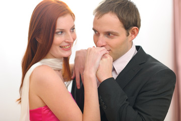Man in suit kissing hands of red hair woman in evening dress
