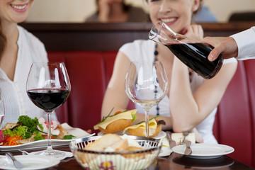 kellner schenkt rotwein ein