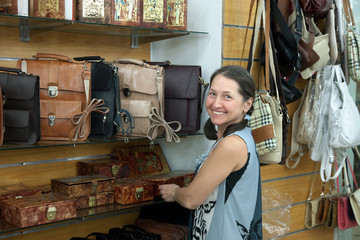 woman chooses leather chest at  shop