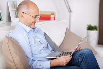entspannter mann mit laptop auf dem sofa