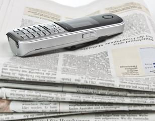 Informationen Telefon liegt auf Zeitungen