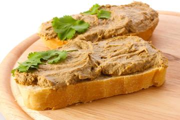 Fresh pate on bread on wooden board