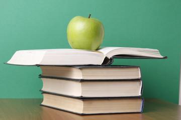an apple over books