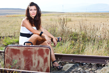 Young woman sitting on railroad