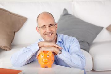 lächelnder mann hält sein sparschwein fest