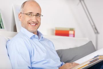lächelnder mann mit aktenorder auf dem sofa
