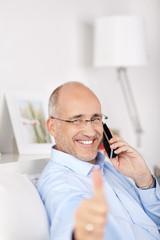 lächelnder mann am telefon zeigt daumen hoch