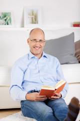 entspannter mann sitzt lesend im wohnzimmer
