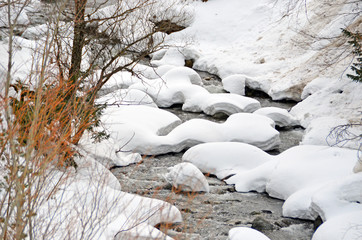 stones with snow hat in the river