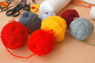 Colorful woolen yarns and scissors on the table