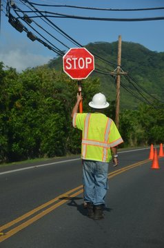 worker with yellow west holds stop sign