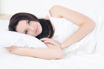 Young woman lying in bed, looking rested and relaxed