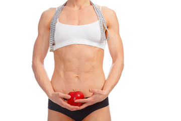 Muscular woman with apple and tape measure posing against white