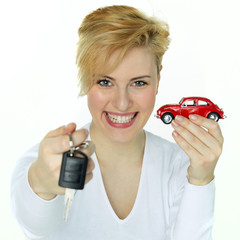 Young woman is proud to have a new red car