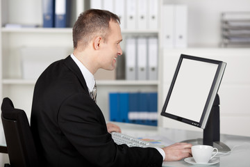 geschäftsmann im büro schaut auf seinen bildschirm