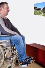 Mann im Rollstuhl schaut Bild an