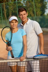 Attractive couple smiling on tennis court