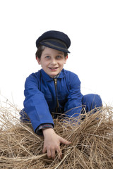 boy in blue coverall and cap harvesting straw