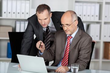 zwei kollegen besprechen etwas am laptop