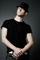 Handsome man posing in black t-shirt and black hat.