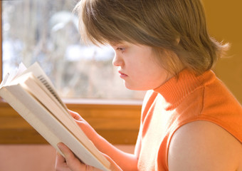 A girl with Down syndrome reading.