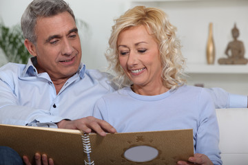 Middle-aged couple looking through photo-album