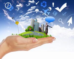 Human hand holding a green landscape
