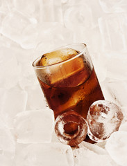 Glass of cool cola on ice background