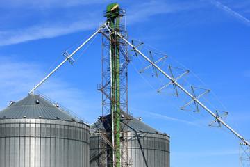 Metal Grain Bins Against A Blue Sky