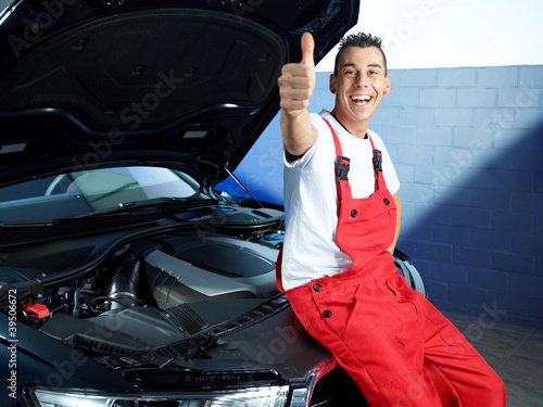 Happy apprentice in a garage sitting on a car shows thumb for Garage happy car