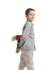 mothers day: boy hiding a bouquet of flowers behind his back
