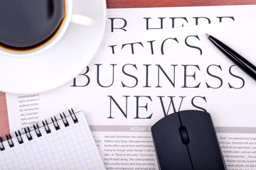 Business newspaper, notebook, mouse and cup of coffee