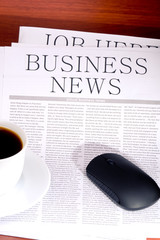 Business newspaper, cup of coffee and mouse
