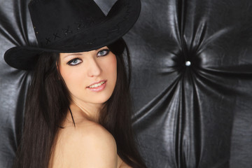 Young sexy woman in cowboy hat over dark