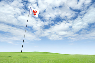 Golf flag at hole 18 on the putting green