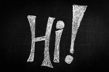 """""""Hi"""" written on a black chalkboard"""