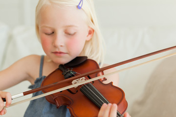 A talented little girl slowly plays the violin