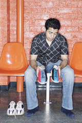 Man putting on bowling shoes