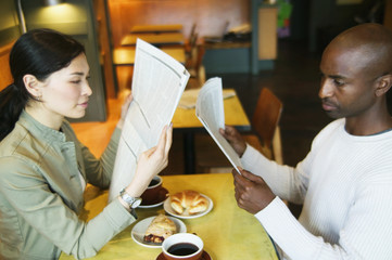 Couple reading newspaper in restaurant