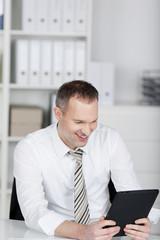 lächelnder geschäftsmann blickt auf seinen tablet-computer