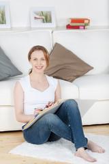 lächelnde junge frau mit aktenorder im wohnzimmer