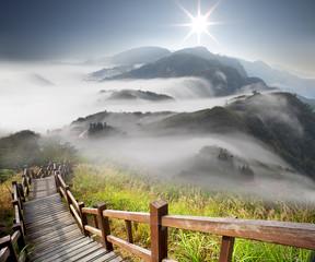 Obraz premium Dramatyczne chmury z górą i drzewem
