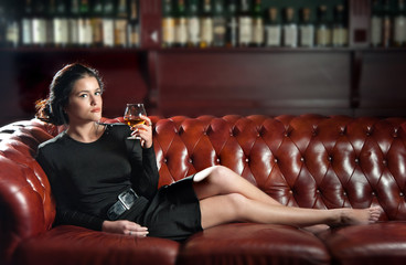 Young woman with a glass of brandy
