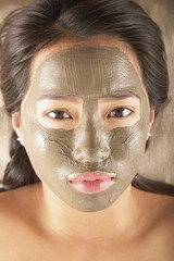 Young woman posing with mud mask facial