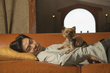 Portrait of man laying on couch with dog