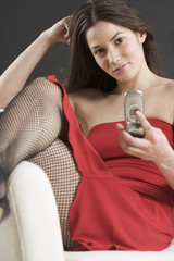 Portrait of woman in red dress holding cell phone